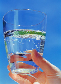 Hand holding glass of sparkling water with lime slice